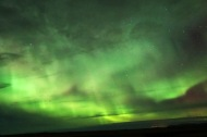 The bright dancing lights of the aurora are actually collisions between electrically charged particles from the sun that enter the earth's atmosphere.
